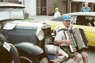 Playing the accordion, on the bumper of his Model A.